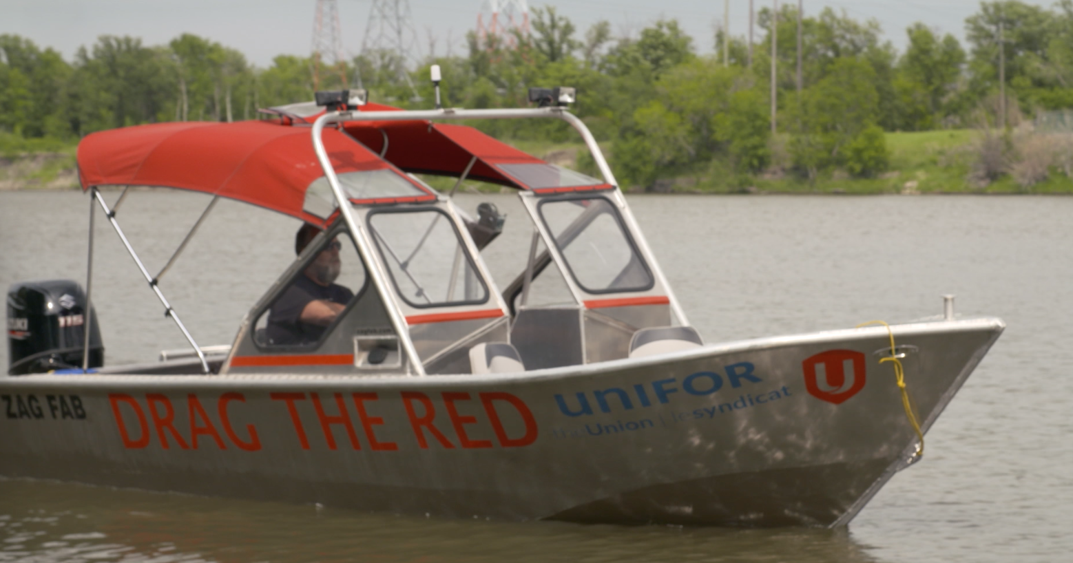 Video screenshot of an aluminum boat with a red canopy on the Red River. The boat says Drag the Red on the side and has a Unifor logo on the hull.